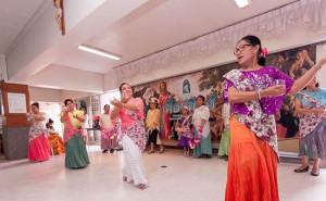 Ms. Vilma is dancing the Binasuan wearing a purple kimona and orange skirt.