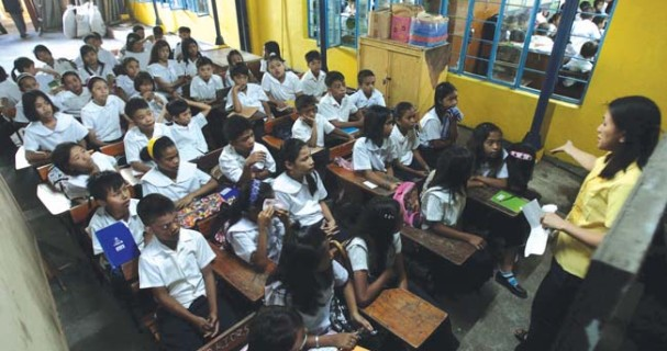 A teacher gives instruction inside a class room in Payatas B elementary school in Quezon city yesterday. An estimated 25.7 million students trooped to schools on Monday to kick off another school year, amid problems of lack of teachers, books, and classrooms in public schools. (KJ ROSALES)